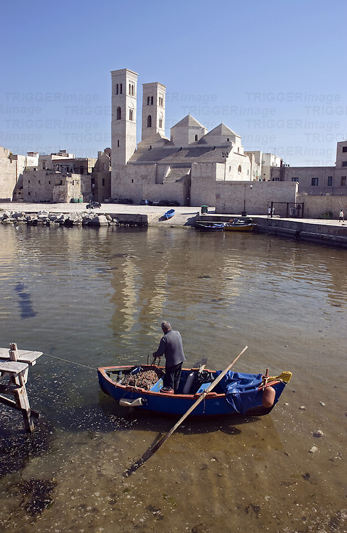 An old man standing in a small fishing boat in a small European harbour
