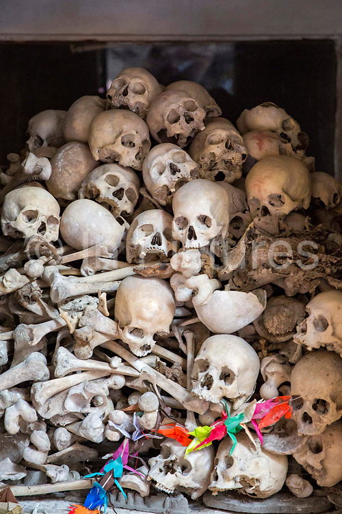 Skulls and bones kept in a glass-covered cabin shrine in a Killing Cave of Phnom Sampeau in Battambang region, Cambodia, South East Asia.  These are some of the people who were butchered to death by the Khmer Rouge Regime in the 1970s and their bodies were thrown into caves.