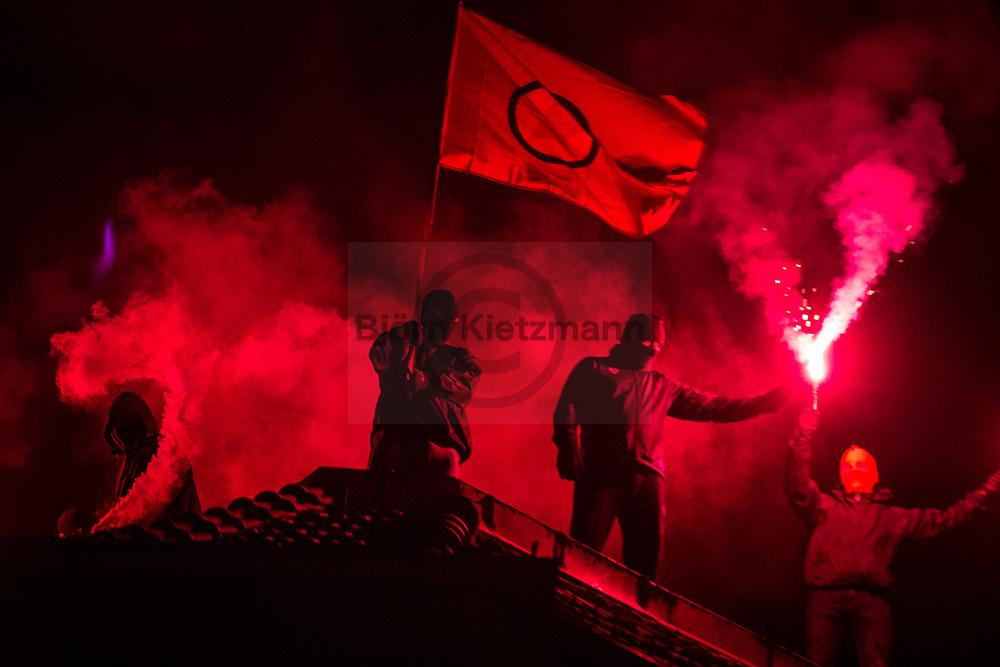 Berlin, Germany - 29.09.2018<br /> <br /> Masked demonstrators waving a PKK flag and burning pyrotechnics on the roof of a house in the Rigaer Strasse. Left-wing demonstration in Berlin-Friedrichshain for the protection of the feminist house project Liebig34 (Liebigstrasse 34). Nearby the demonstration route activists occupied an empty house, which also belonged to the owner of Liebig34.<br /> <br /> Vermummte Demonstranten zuenden Pyrotechnik auf einem Balkon des Hausprojekts Liebig34. Linksradikale Demonstration in Berlin-Friedrichshain fuer den Erhalt des feministische Hausprojekts Liebig34 (Liebigstrasse 34). Am Rande der Demonstration wurde ein leerstehendes Haus besetzt, welches ebenfalls dem Eigentuemer der Liebig34 gehoert.<br /> <br /> Photo: Bjoern Kietzmann