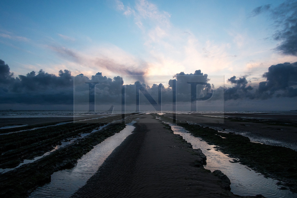 © Licensed to London News Pictures. 26/03/2014<br /> <br /> Redcar, Cleveland, United Kingdom<br /> <br /> Morning light is reflected in long pools of water left behind in the rock scars on the beach at Redcar, Cleveland during at low tide.<br /> <br /> Photo credit : Ian Forsyth/LNP