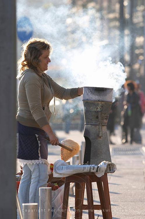 woman selling chestnuts on cais da ribeira porto portugal