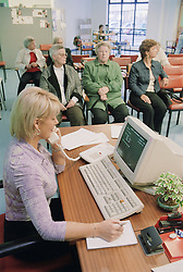 Receptionist sitting at desk in front of computer and talking on telephone in waiting room of Fracture Clinic in hospital,