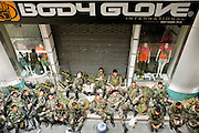 """Apr. 19 2010 - BANGKOK, THAILAND: Thai soldiers relax in front a """"Body Glove"""" store in the Silom financial district in Bangkok Monday. Hundreds of Thai soldiers, including reservists and front line units, and riot police moved into the Silom financial district Monday, not far from the red-shirts' main protest rally site, in Ratchaprasong. The heavy show of force is to prevent the Red Shirts from entering the Silom area. Many of soldiers were greeted as heros by workers in the area, who oppose the Red Shirts.   Photo by Jack Kurtz"""