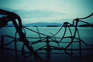 Seascape shot through a decaying metallic fence, Northern Laos, Southeast Asia. The sky and lake are the same color tone.