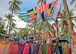 Manuel Antonio National Park, Puntarenas province, Costa Rica: Brightly colored pareos fly in the offshore breeze.  Nature and souvenir vendors vie for attention along Northern Espadilla Beach, immediately outside the entrance to the national park.