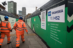 London, UK. 28 January, 2020. Construction workers wearing HS2 jackets pass a sign indicating a site designated for the HS2 project close to Euston station. Cost projections for the high-speed rail link are reported to have risen to £106bn and the Government is expected to make a decision regarding its viability this week.