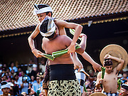 22 JULY 2016 - TENGANAN DUAH TUKAD, BALI, INDONESIA:  Boys engage in pandanus fights in the Tenganan Duah Tukad village on Bali. The ritual Pandanus fights are dedicated to Hindu Lord Indra. Men engage in ritual combat with spiky pandanus leaves and rattan shields. They usually end up leaving bloody scratches on the combatants' backs. The young girls from the community wear their best outfits to watch the fights. The fights have been traced to traditional Balinese beliefs from the 14th century CE. The fights are annual events in the Balinese year, which is 210 days long, or about every seven months in the Gregorian calendar.   PHOTO BY JACK KURTZ
