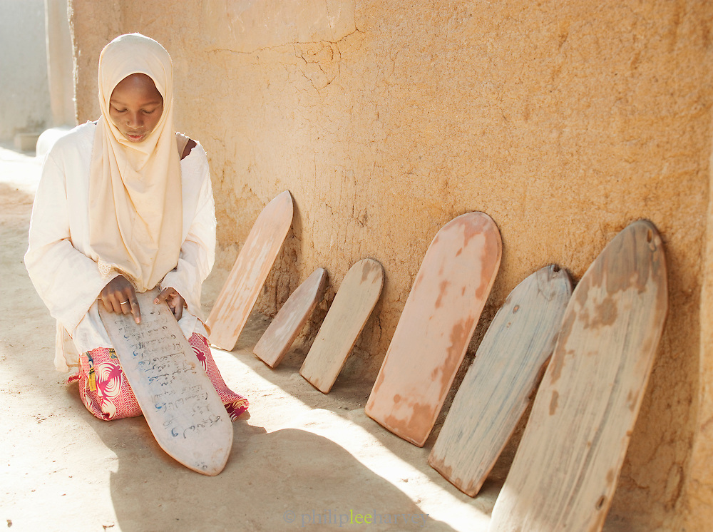 A girl learning scripture from the Koran at the Koranic school in Djenné, Mali