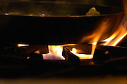 Blue and yellow gas fire flames burner on a cast iron professional restaurant kitchen stove, frying pan. The Dolly Irigoyen - famous chef and TV presenter - private restaurant, Buenos Aires Argentina, South America Espacio Dolli