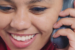 Young woman using mobile phone smiling,