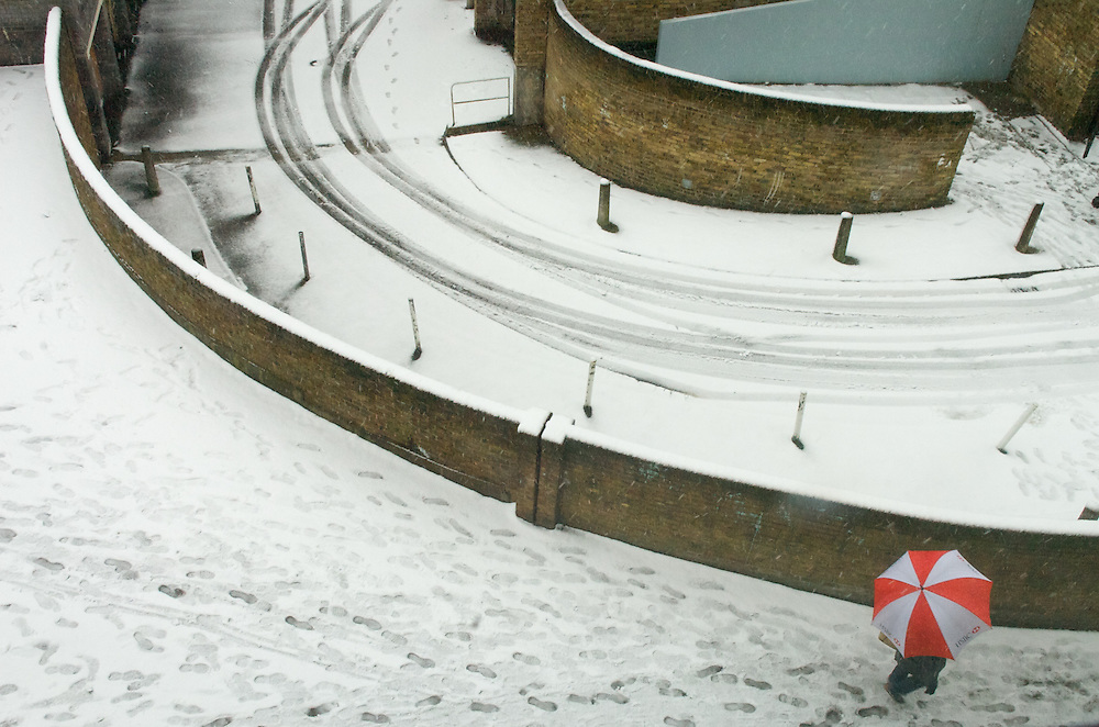 A lone pedestrian trudges through the London snow. in Mile End