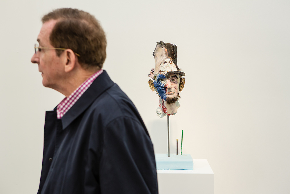 New York, NY - 5 May 2017. The opening day of the Frieze Art Fair, showcasing modern and contemporary art presented by galleries from around the world, on Randall's Island in New York City. A man walks by a creepy mixed-media head of Abraham Lincoln by David Altmejd in the gallery of Xavier Hufkens.