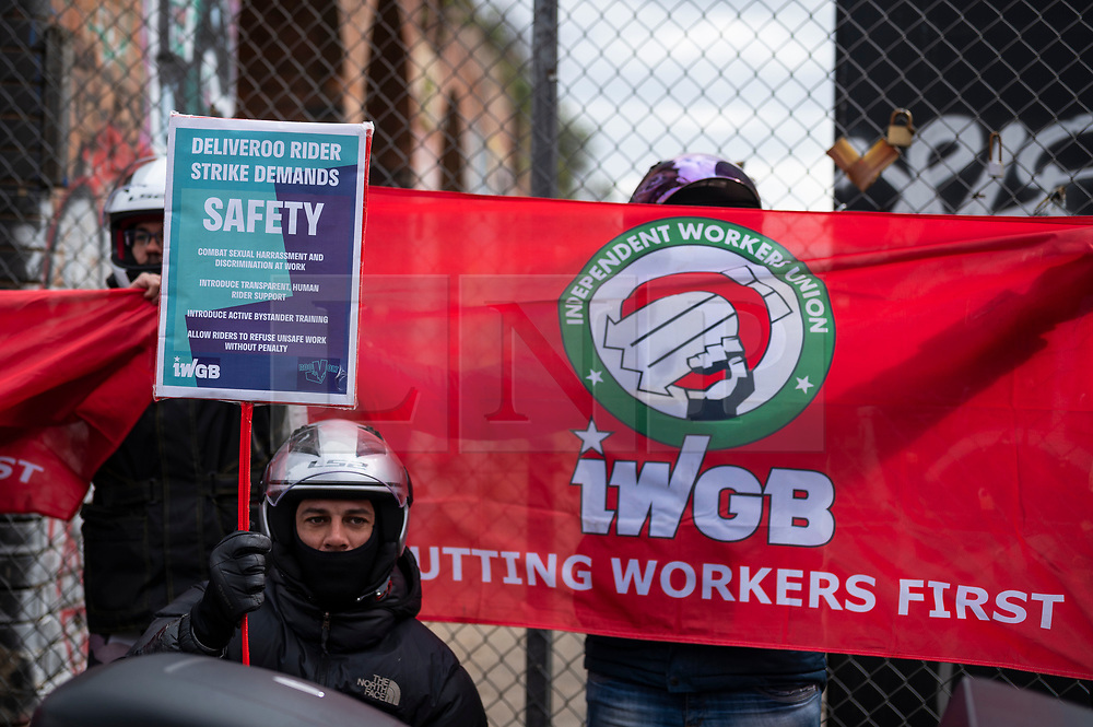 © Licensed to London News Pictures. 07/04/2021. LONDON, UK.  Deliveroo riders and drivers on strike stage a protest outside Shoreditch station against the company demanding improvements to pay and conditions in terms of minimum wage, holidays and sick leave.  The strike comes on the same day that the company's shares are publicly traded for the first time following its initial public offering (IPO) on 31 March, where shares fell by 25% after failing to receive support by institutional investors who cited concerns about the company's policy on workers' rights.  Photo credit: Stephen Chung/LNP