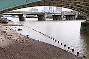 With the wooden piles of old warves and quays revealed in the low tidal waters of the Thames, a member of the public explores the river's foreshore beneath Southwark Bridge, on 13th September 2021, in London, England. Excavating the Thames foreshore is only allowed by licensed 'Mudlarkers' who scour the mud and shingle for historical artefacts dated from throughout London's history as a port and ancient settlement.