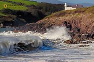 Waves crash into cliffs below Dingle Lighthouse at Binn Ban Beach near Dingle, Ireland