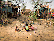 """01 MARCH 2014 - MAE SOT, TAK, THAILAND: Children play on the ground in front of their home in a small Burmese community in the forest a few kilometers north of Mae Sot. Mae Sot, on the Thai-Myanmer (Burma) border, has a very large population of Burmese migrants. Some are refugees who left Myanmar to escape civil unrest and political persecution, others are """"economic refugees"""" who came to Thailand looking for work and better opportunities.    PHOTO BY JACK KURTZ"""