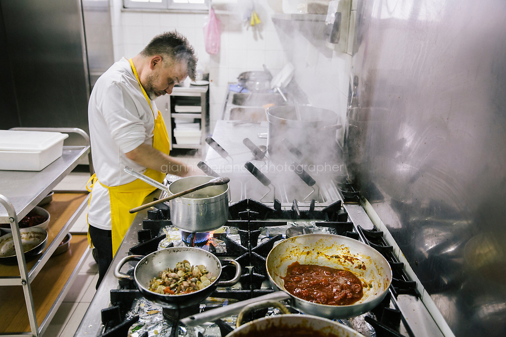 NAPLES, ITALY - 20 MARCH 2018: Carmine Esposito checks the pasta in the kitchen at the Pizzeria e Trattoria Vigliena in Naples, Italy, on March 20th 2018.<br /> <br /> Pizzeria e Trattoria Vigliena is a restaurant outside of the city center and adjacent to the port. At lunch, the place is packed with workers from the docks and ship owners and workers from the recently built Marina Vigliena.<br /> <br /> The restaurant is owned by Raffaele Esposito, Concetta's son and the third generation of a family of chefs who founded this restaurant in the middle of the 20th century