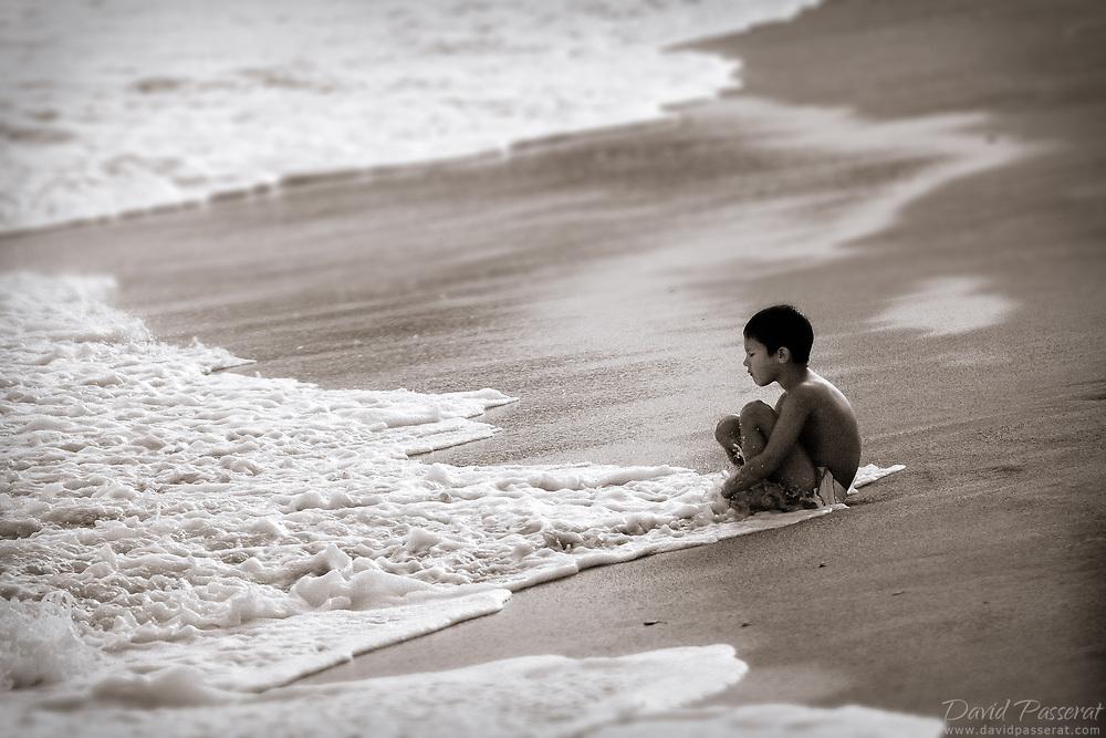 Boy sitting on the beach.