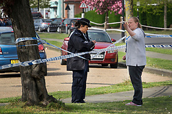 © Licensed to London News Pictures. 12/04/2017. London, UK. A police officer takes a statement from a local woman near Newnham Close where a 19 year old man, named locally as Abdullahi Tarabai,  was murdered yesterday after reportedly being chased though a housing estate in Northolt. This is the second fatal stabbing in the capital in 24 hours. The location is adjacent to a gun siege from October 2016. Four men have been arrested Photo credit: Peter Macdiarmid/LNP