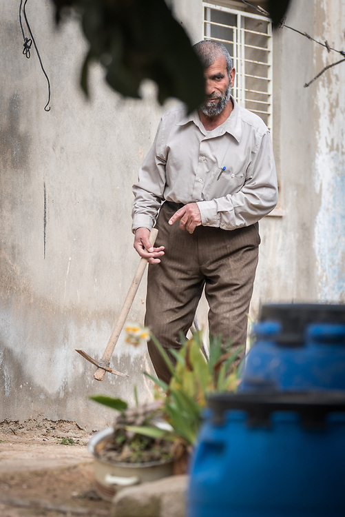 16 February 2020, Irbid, Jordan: Mahmoud Al-Omari carries a hatchet through his garden in Al-Mazar. He is one of many beneficiaries to recently have received support from the LWF in setting up home-based farming in the area of Al-Mazar. By providing tools and seeds, the project has helped 150 families grow food for themselves and, in some cases, also earn an income from selling their surplus at local markets.