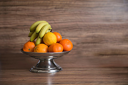 Close-up of fruit bowl of oranges and bananas on table, Munich, Bavaria, Germany