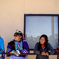 Alandra Dewa, left, Erica Chopito, Naomi David and Mya Eraicho watch the festivities during the Indigenous Peoples' Day celebration at Six Directions School in Gallup Monday.