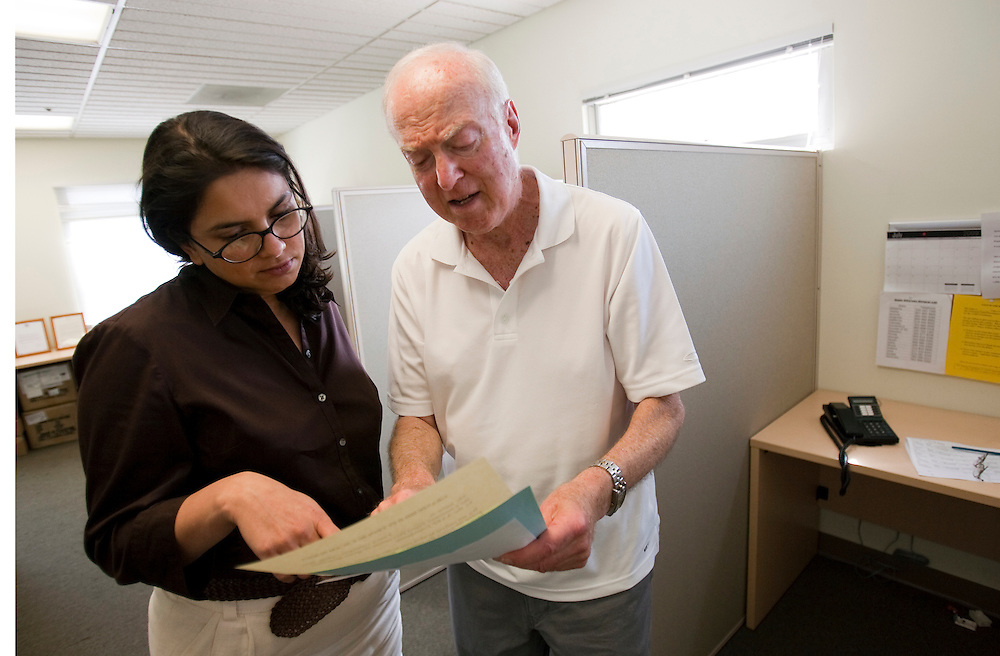 Barry Greenberg, who volunteers as Fraud Fighters at the WISE and Healthy Aging facility in Santa Monica, CA, discusses a phone script with manager Petula Storey in the call center where they phone senior citizens to warn them of phone fraud.