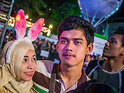 31 DECEMBER 2012 - BANGKOK, THAILAND: A Thai Muslim couple attends the New Year's Eve party in Ratchaprasong Intersection in Bangkok. The traditional Thai New Year is based on the lunar calender and is celebrated in April, but the Gregorian New Year is celebrated throughout the Kingdom, especially in larger cities and tourist centers, like Bangkok, Chiang Mai and Phuket. The Bangkok Countdown 2013 event was called ?Happiness is all Around @ Ratchaprasong.? All of the streets leading to Ratchaprasong Intersection were closed and the malls in the area stayed open throughout the evening.    PHOTO BY JACK KURTZ