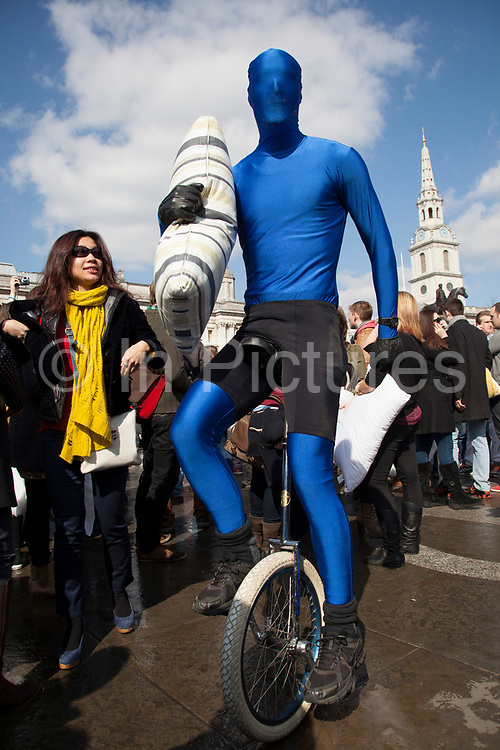 London, UK. Saturday 6th April 2013. World Pillow Fight Day in London, UK. Man in a blue Morph Suit riding a unicycle. . This flashmob event is organised by the Urban Playground Movement. A pillow fight flash mob is a social phenomenon of flash mobbing and shares many characteristics of a culture jam.