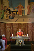 Priest gives blessings during Mass at St. Lawrence's Catholic church in Feltham, London.