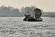 Nederland, Millingen, Nijmegen, 8-4-2020 Vandaag werd een replica van een Romeins masker vervoerd van de scheepswerf in Millingen aan de Rijn naar Het Lentereiland in de nevengeul bij Nijmegen. Het beeld van 6 meter hoog wordt daar geplaatst om als blikvanger en uitkijkpunt te dienen voor de oude stad. Het origineel bevindt zich in museum het Valkhof. De maker en ontwerper is kunstenaar Andreas Hetfeld . Foto: Flip Franssen