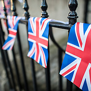 Small Union Flag pennants draped over a black wrought iron fence in Bath, Somerset, United Kingdom.