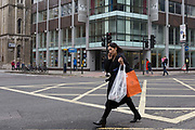 A woman uses her mobile phone outside the offices of Cambridge Analytica on New Oxford Street, the UK tech company accused of harvesting the personal details of Facebook users in its data privacy scandal, on 11th April, 2018, in London, England.