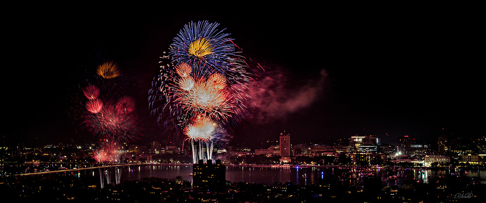The July 4, 2018 Boston Massachusetts fireworks celebration lights the sky over Cambridge, Massachusetts.  Over 10,000 pyrotechnic explosions initiated by over 4,000 computer comands originate from barges in the Charles River and the Massachusetts Avenue bridge.  The fireworks can soar as high as 1,500 feet into the summer night sky.  This spectacular event has been a tradition in Boston since 1974.