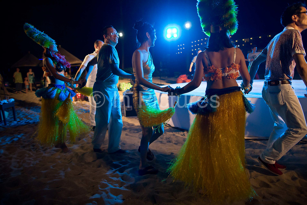 Participants of Diamond Love, a high-end dating service, dance while attending a beach dinner party in Sanya, Hainan Province,  China on15 June  2013.  Male participants of the dating service pay up to 20,000 USD to attend such events in hopes of finding a suitable match while most of the women are selected by the match making service according to their looks, education, and personality.
