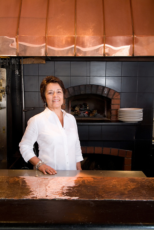Owner of a restaurant on the Pearl St. Mall in Boulder, Colorado in front of her pizza oven.