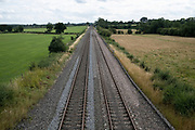 Train tracks disappering into perspective and distance on 1st August in Hanbury, United Kingdom. This piece of track, viewed from above is running through agricultural fields.
