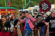New York Brass Band stomping through Glastonbury festival.<br /> Glastonbury Festival is the largest greenfield festival in the world, and is now attended by around 175,000 people. It's a five-day music festival that takes place near Pilton, Somerset, England. In addition to contemporary music, the festival hosts dance, comedy, theatre, circus, cabaret, and other arts. It is organised by Michael Eavis on his own land, Worthy Farm in Pilton. Leading pop and rock artists have headlined, alongside thousands of others appearing on smaller stages and performance areas.