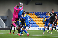AFC Wimbledon striker Joe Pigott (39) battles for possession with Lincoln City goalkeeper Alex Palmer (1) during the EFL Sky Bet League 1 match between AFC Wimbledon and Lincoln City at Plough Lane, London, United Kingdom on 2 January 2021.