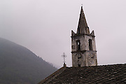 Church steeple with bell and clock and a cross on the roof next to it. Some trees on hillside beyond on a grey foggy day, Usseaux is a comune or municipality in the Province of Turin, Piedmont. A rustic village in the Italian Alps.