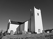 """Ballintoy Parish Church was built in 1813, which background was the harbour and Rathlin Island. The area has been the filming site of the award winning TV series """"Game of Thrones""""."""