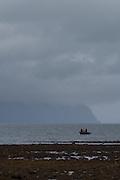 Firsherman on boat under storm clouds in Rescurrection Bay, Seward, Alaska