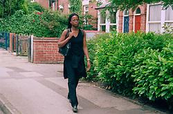 Young woman walking down street carrying shoulder bag,