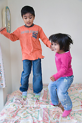 Sister and brother bouncing on the bed,
