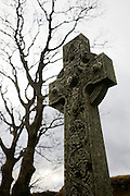 Old stone cross at the old church at Kilninian Church. The old church at Kilninian (built 1755, ten years after the Jacobite Rising)  but the site of worship with medieval tombstones dating from the 14th century, Kilninian, Isle of Mull, Scotland. church is one of the oldest, and until very recently, still used for worship.   Possibly standing on the site of an earlier medieval church, it first appears in the records of 1561, where it is stated that the parsonage of 'Keilnoening' had formerly belonged to the Abbot of Iona, one-third of the revenues going to the Bishop of the Isles as was customary in the diocese. Iona Abbey would have appointed a minister for the church at a stipend lower than the tithes. It is uncertain whether the church was dedicated to St Ninian, the apostle of Galloway, or to a local saint of the Early Christian period'.   It is also believed to have been once known as the Chapel of the Nine Maidens and in Gaelic  'Cill Naoi Nighean', although another possible name was The Church of the Holy Maidens - 'Cill Naoimh Nighean...(http://www.undiscoveredscotland.co.uk/mull/kilninianchurch/index.html)