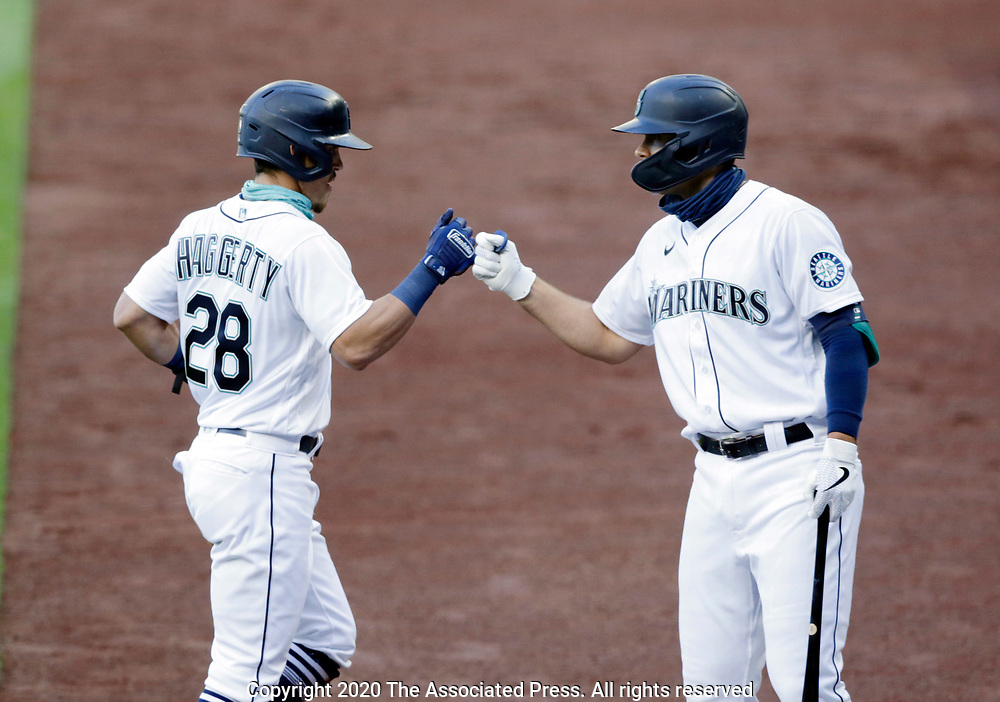 Seattle Mariners' Sam Haggerty is congratulated by Evan White after scoring on an sacrifice fly hit by Kyle Seager against the Texas Rangers during the first inning of a baseball game, Saturday, Aug. 22, 2020, in Seattle. (AP Photo/John Froschauer)