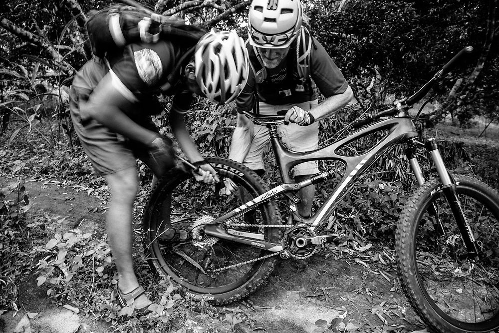 Andrew Whiteford and Win Jalawin fix a flat tire on the single track in the jungle near Chiang Mai, Thailand.
