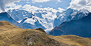 """Hiking trails above Pontresina give good views of Piz Palü (3901 meters or 12,799  feet) and the Bernina massif, in Upper Engadine, Grison Alps, Switzerland, Europe. The Swiss valley of Engadine translates as the """"garden of the En (or Inn) River"""" (Engadin in German, Engiadina in Romansh, Engadina in Italian). Panorama stitched from 2 overlapping images."""