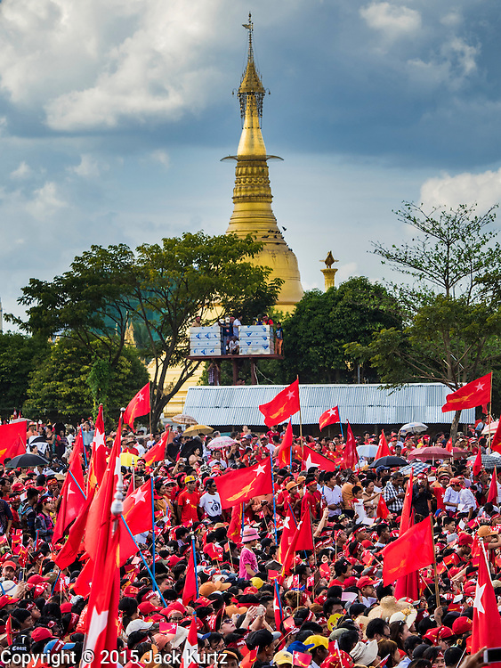 01 NOVEMBER 2015 - YANGON, MYANMAR: The crowd waits for Aung San Suu Kyi at the NLD's last election rally of the 2015  election in the Yangon suburbs Sunday. Thuwunna Pagoda is in the background. Political parties are wrapping up their campaigns in Myanmar (Burma). National elections are scheduled for Sunday Nov. 8. The two principal parties are the National League for Democracy (NLD), the party of democracy icon and Nobel Peace Prize winner Aung San Suu Kyi, and the ruling Union Solidarity and Development Party (USDP), led by incumbent President Thein Sein. There are more than 30 parties campaigning for national and local offices.    PHOTO BY JACK KURTZ