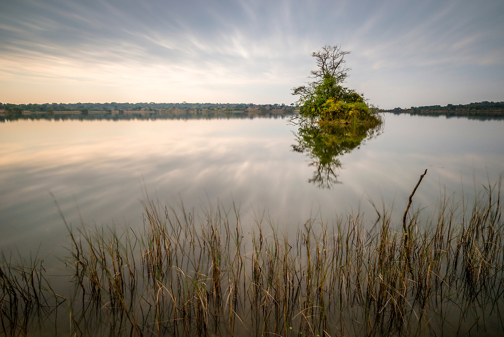 Long exposure image of the green isle in Wamami Lake with streaky clouds refelcted in still water and water grasses in the foreground